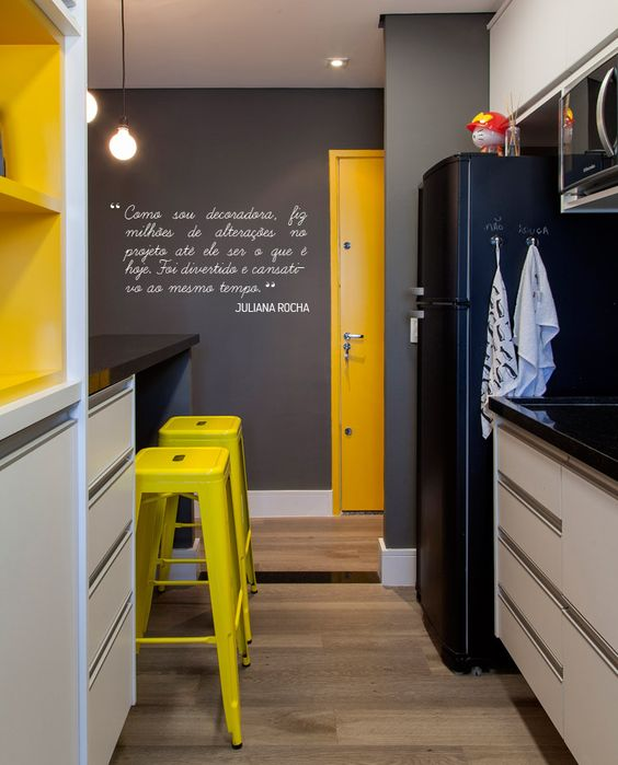 a very small black, white and yellow kitchen with a black fridge and walls, black countertops and touches of various yellow shades