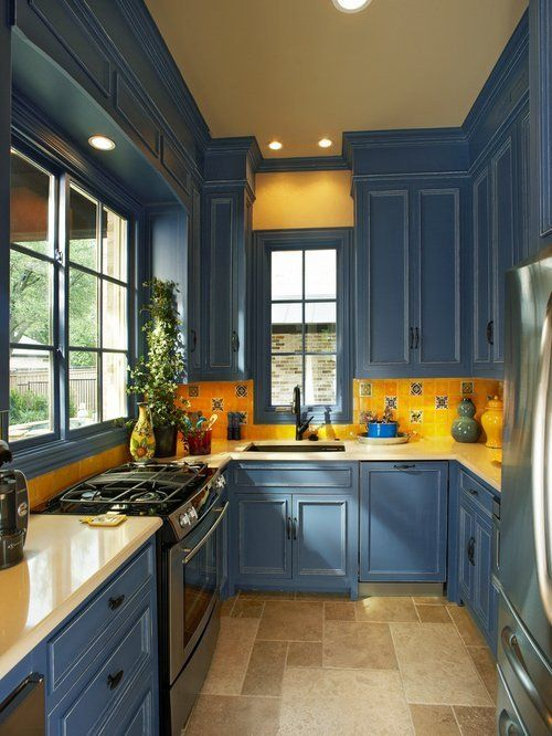 a vintage blue and bright yellow kitchen with a mosaic tile backsplash and built-in lights looks chic and elegant