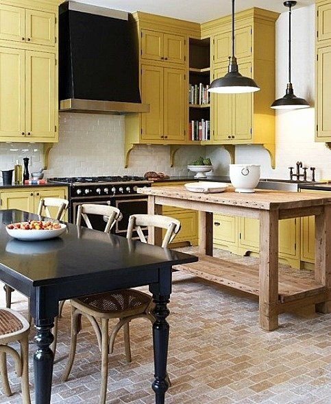 a vintage kitchen done in black, pale yellow and white, with pendant lamps and vintage and rustic furniture