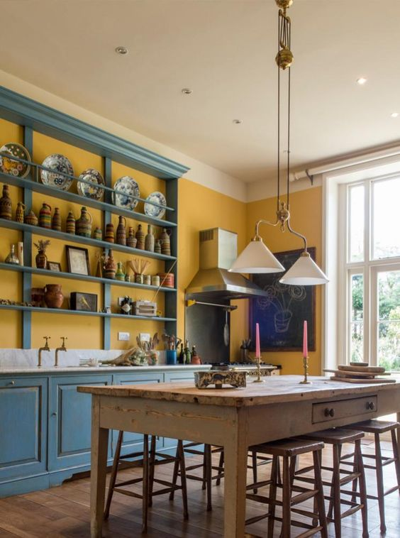 a vintage kitchen done in buttercream and with blue cabinets and open shelving, with vintage pendant lamps and a rustic dining set