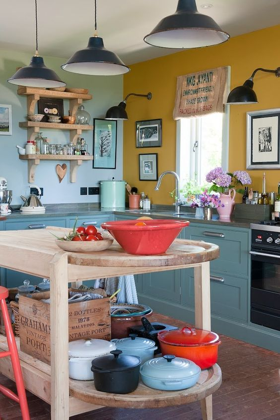 a vintage kitchen with blue cabinets, a mustard and a light blue wall, a wooden kitchen island and black pendant lamps