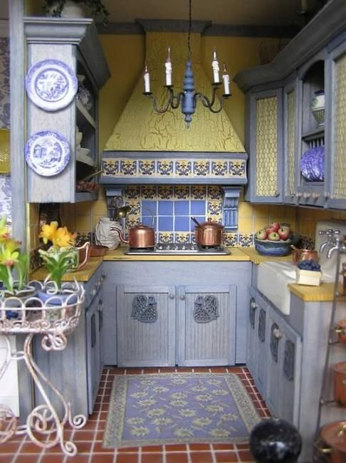 a vintage kitchen with light blue cabinets, bright yellow surfaces and mosaic tiles and plates with yellow and blue
