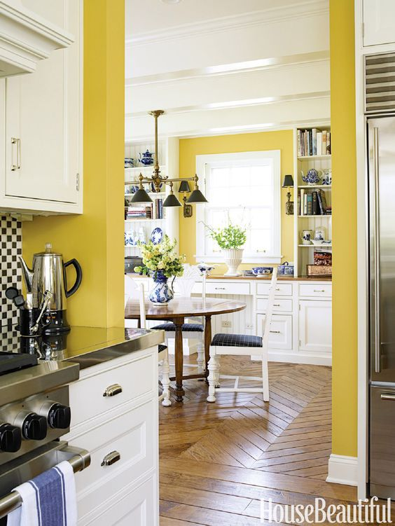 a vintage kitchen with sunny yellow walls, white cabinetry, black and navy touches for a bright contrast and bold looks