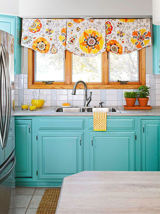 a vintage turquoise kitchen with a white tile backsplash, a bright pritned curtain and a white stone countertop