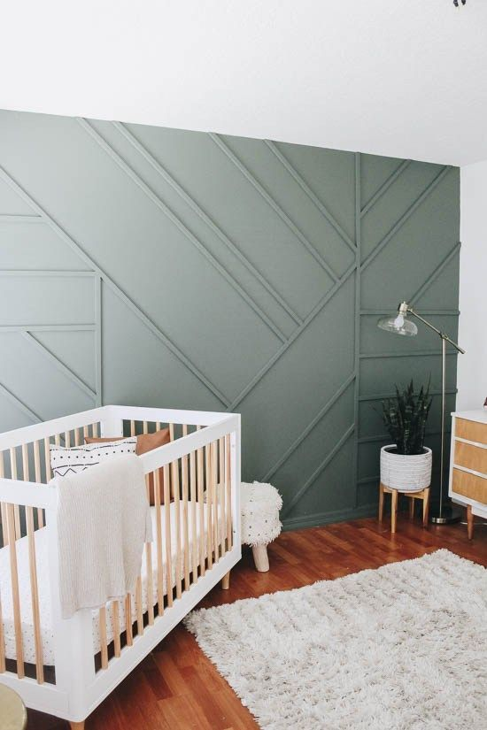 a welcoming rustic boho nursery with a green paneled wall for a chic and stylish statement plus a touch of natural color