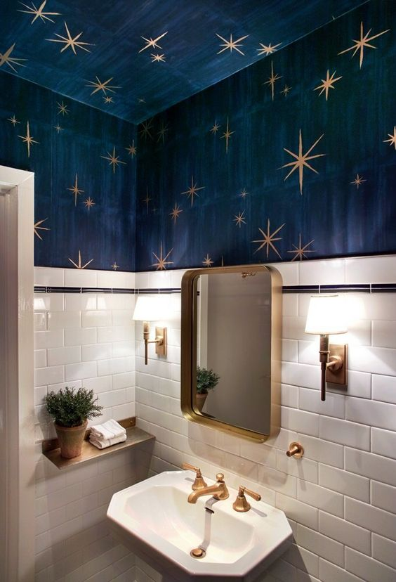 a whimsy powder room with white tiles, navy walls and a ceiling, gold stars, gold fixtures and a gold frame mirror