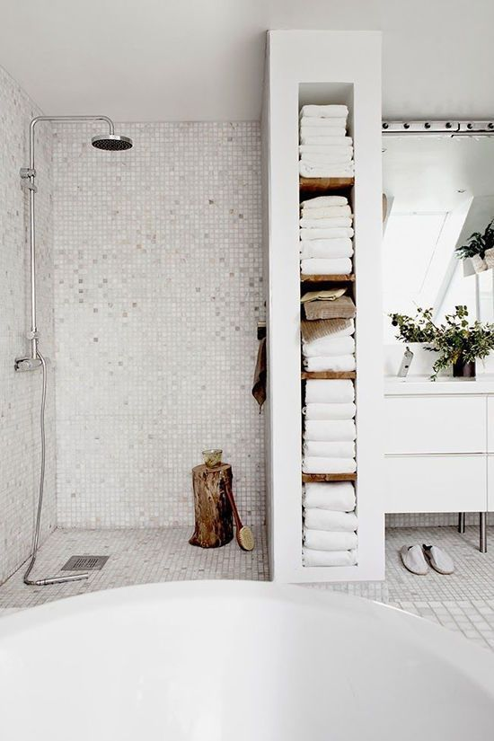 a white Scandinavian bathroom with small tiles, a tub, a pretty towel storage unit and a white vanity vanity