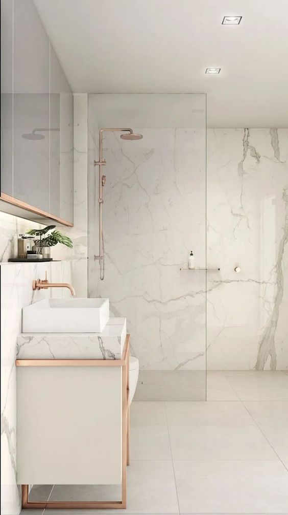 a white bathroom clad with marble, with large scale tiles, with a marble vanity and touches of copper here and there