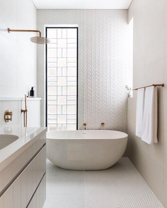 a white bathroom done with various types of tiles, an oval tub, two windows for light and a floating vanity