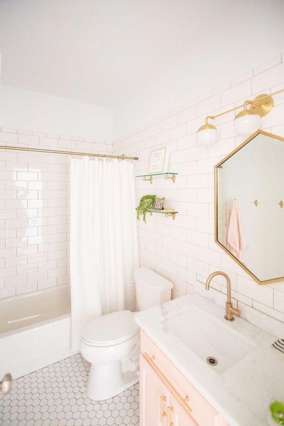 a white bathroom with a gold frame hexagon mirror, gold sconces, fixtures and a curtain rod