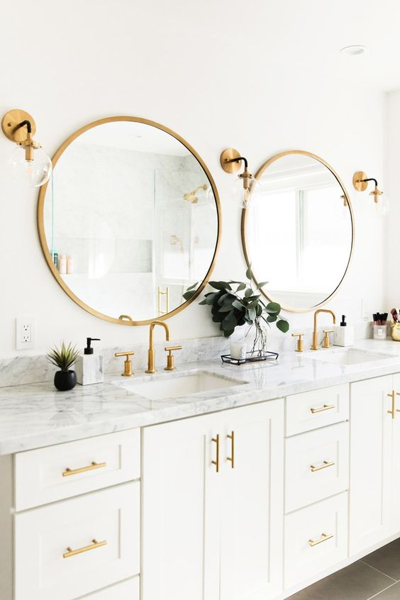 a white bathroom with a large double vanity, a marble countertop, godl framed mirrors, handles and sconces looks nice