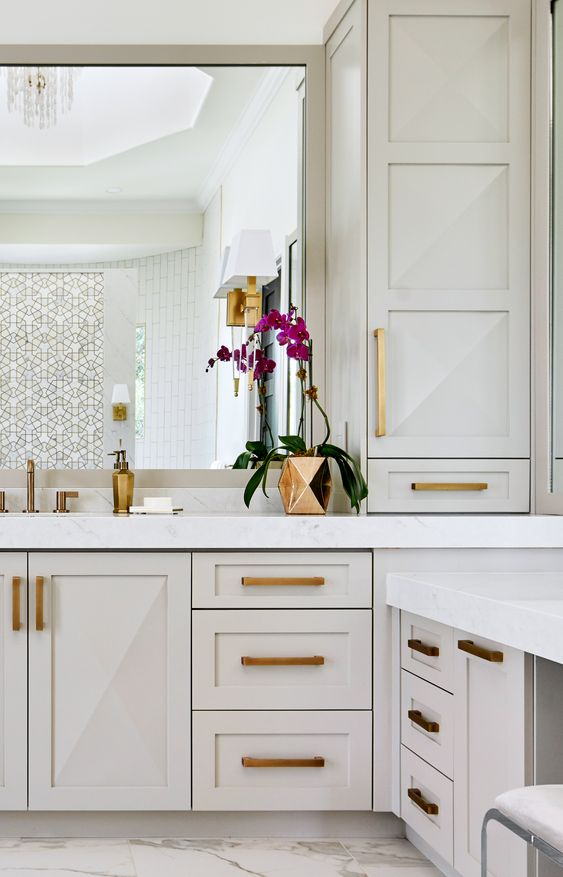 a white bathroom with an oversized vanity and storage units, gold and brass handles, gold fixtures and accessories