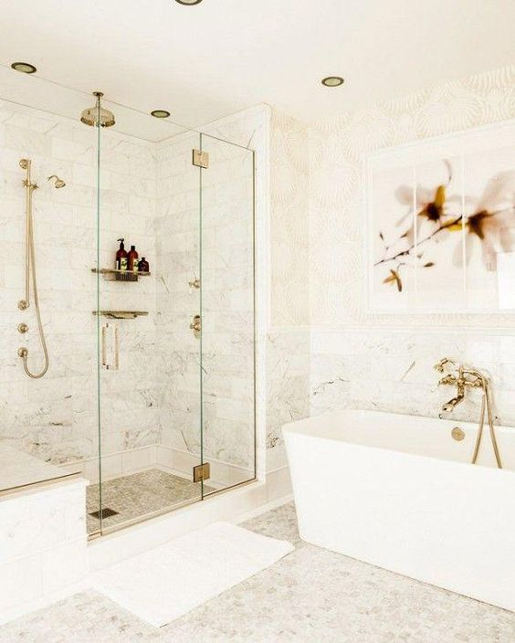 a white bathroom with different tiles, gold fixtures and sconces plus a pretty floral artwork