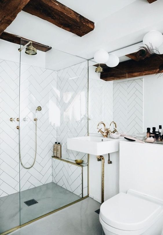a white bathroom with herringbone clad tiles, gold and brass fixtures, dark stained beams and bubble lamps