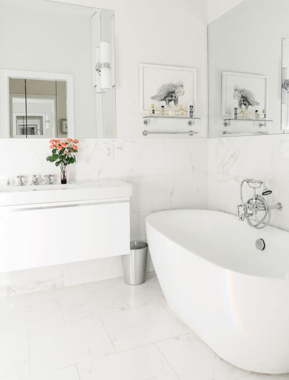 a white bathroom with large scale marble tiles, a tub, a floating vanity and a couple of mirrors