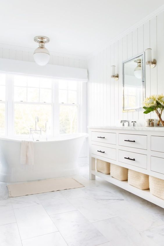a white bathroom with shiplap walls, white marble tiles on the floor and a tub by the window looks very airy
