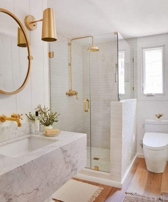 a white bathroom with various kinds of tiles, a floating marble vanity, gold and brass fixtures and sconces looks chic