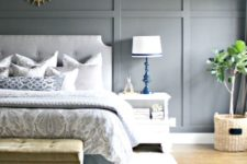 an airy bedroom with a light grey paneled wall, upholstered furniture, printed textiles and rugs plus chic bold lamps