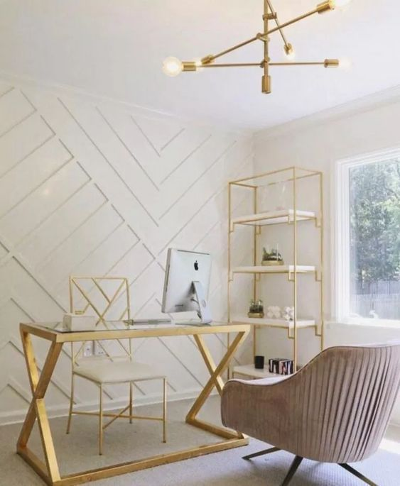 an airy feminine home office with a white paneled wall, gold furniture, a stylish chandelier and a pink chair