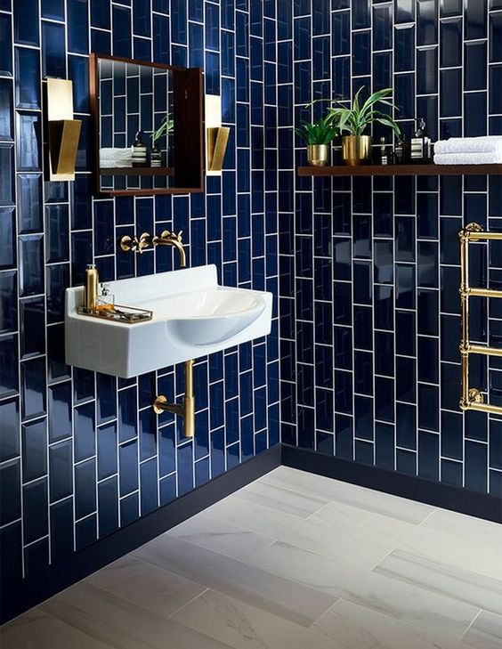 an elegant bathroom clad with navy tiles, spruced up with gold fixtures, lamps and accessories