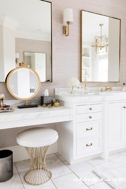 an elegant bathroom with a white vanity with a marble countertop, gold framed mirrors, a gold stool and sconces for accents