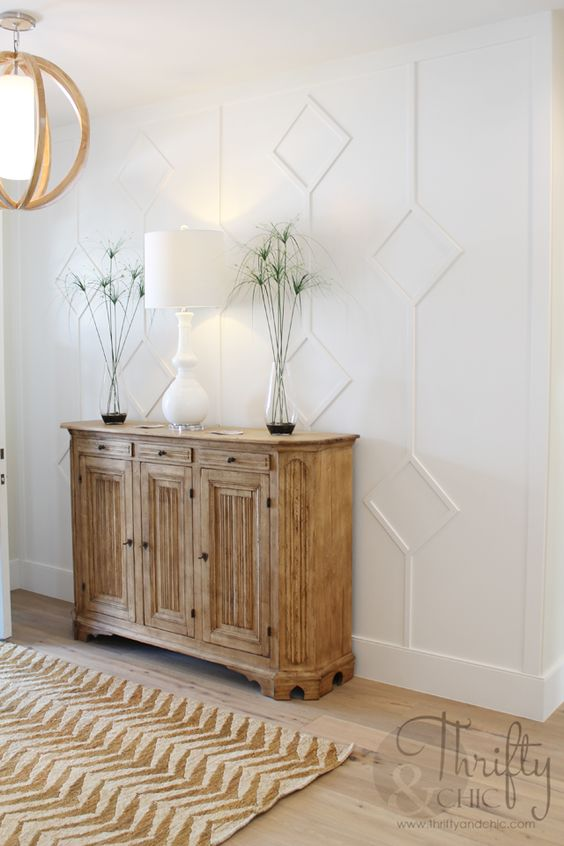 an elegant farmhouse entryway with a white paneled wall, a wooden sideboard and chandelier, a white lamp and greenery