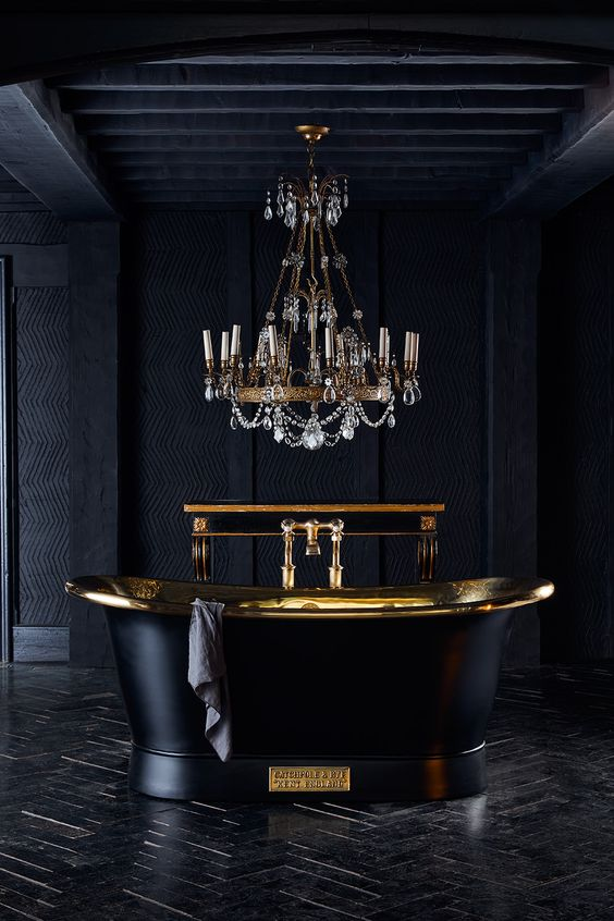 an exquisite black and gold bathroom clad with tiles and done with textural wallpaper, with a black tub and a chic chandelier with crystals