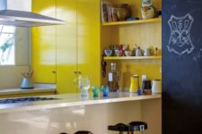 bright yellow cabinetry, a chalkboard wall, black stools, a white built-in kitchen island for a bold modern look