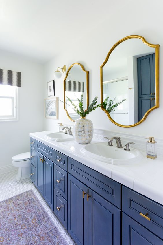 white as the main color, a bold blue vanity, gold fixtures, catchy mirrors in gold frames for a super chic look
