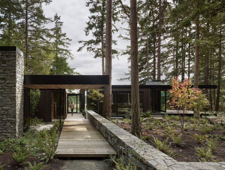 This gorgeous forest home is done in minimalist style, with all the trees preserved on the site