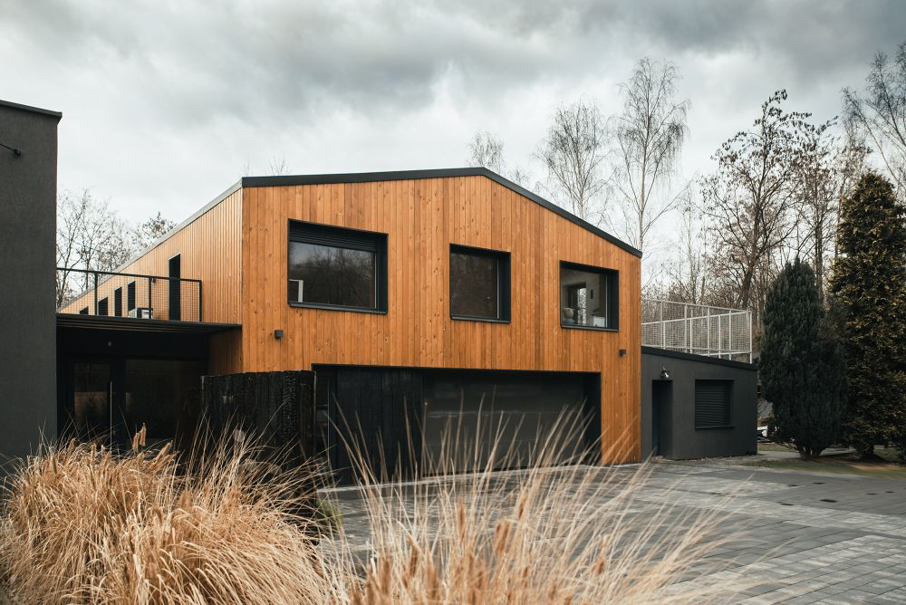 This modern barn home was built using the remnants of the 70s structure and looks bold and contrasting