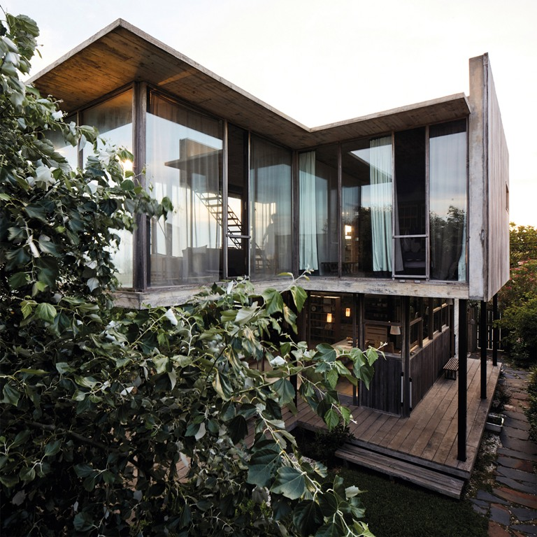 The house features much weathered wood and concrete, and it opened to outdoors