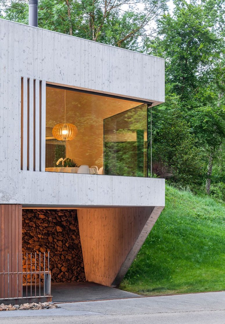The house is clad with light-colored wood, there are glazed walls that allow enjoying the views