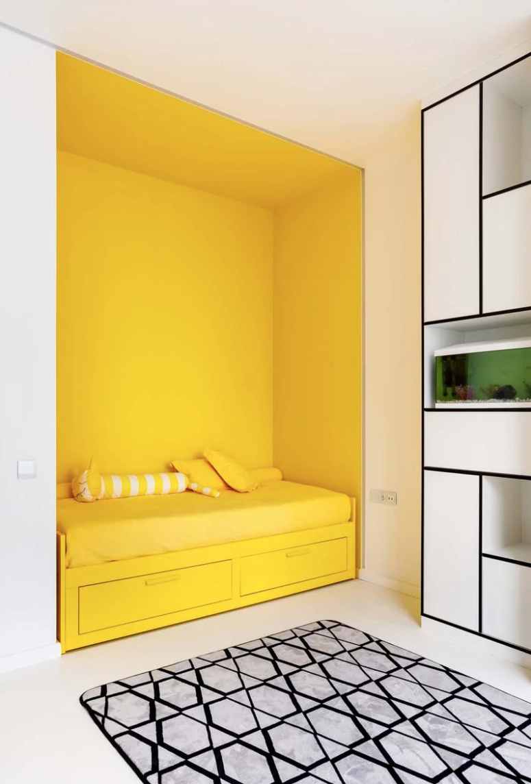 The kid's room shows off graphic decor, a black and white color scheme and colorful accents - a yellow bed niche and a green touch