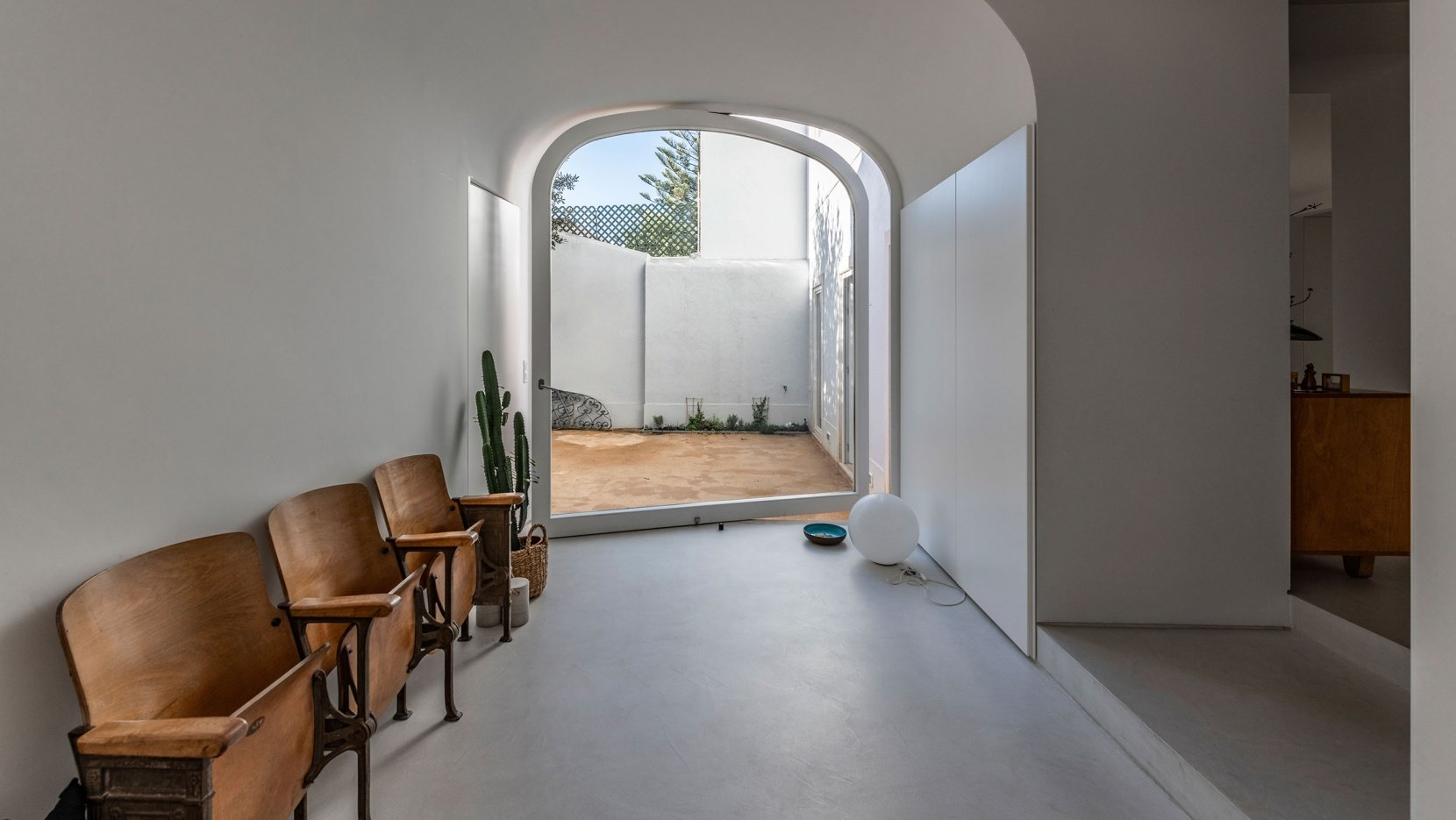 This is an entrance to the inner courtyard, with a pivot door and vintage wooden chairs