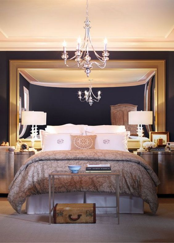 a chic modern bedroom with an oversized mirror in a gold frame, a chic chandelier and a couple of lamps for a refined feel