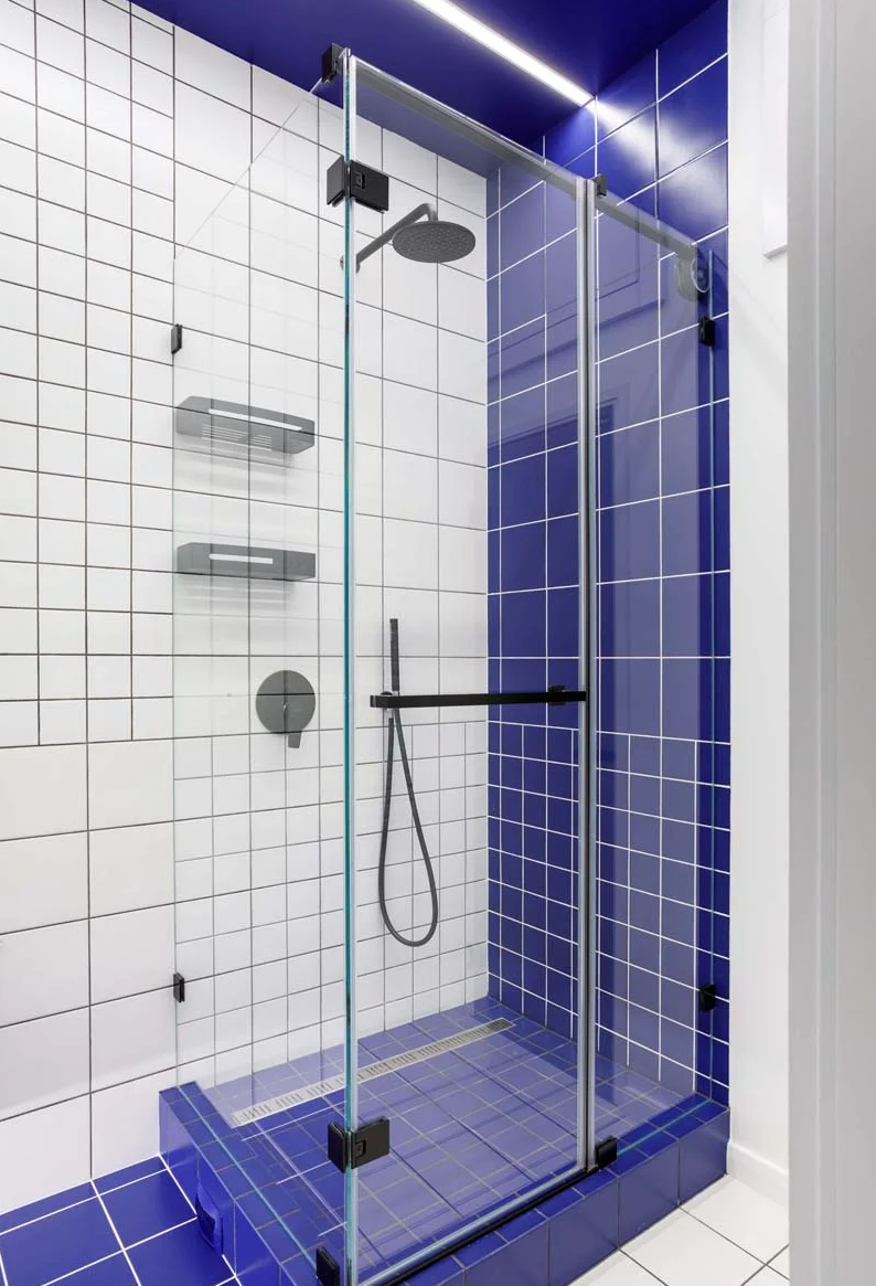The bathroom is done with white tiles, black grout for achieving a graphic look and bold blue tiles for an accent