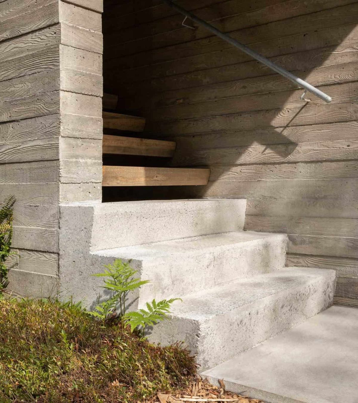 The entrance staircase is built of concrete and wood, with metal railing for a modern feel
