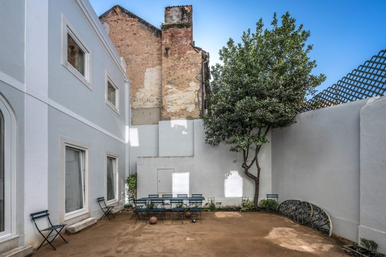 The inner courtyard features some greenery, a living tree, a simple dining set