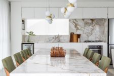 03 The kitchen is done with minimalist white cabinets, a marble backsplash, the dining space is next to it echoing the design with a fabulous marble dining table