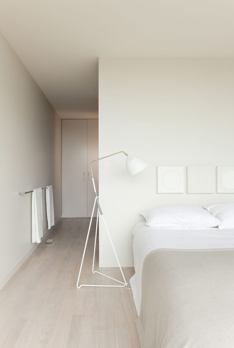 The master bedroom is all neutral, with closed and hidden storage, a large bed, floor lamps and neutral textiles