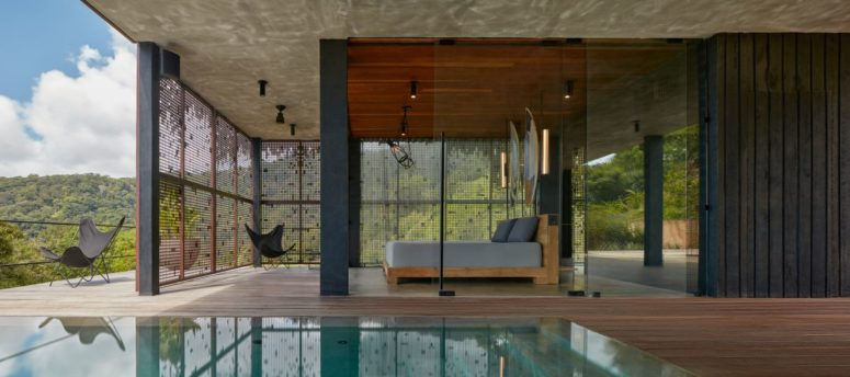 The spaces are indoor-outdoor, with a pool and a deck to which the indoor spaces open
