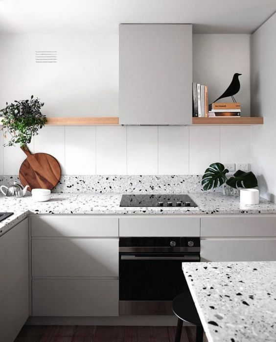 a minimalist kitchen in dove grey accented with a grey terrazzo countertop and backsplash plus a matching table here