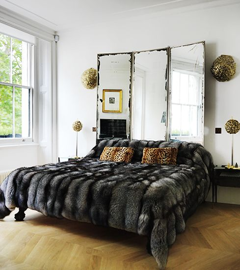 a modern luxurious bedroom with a vintage mirror as a headboard, a faux fur bedspread and some touches of gold