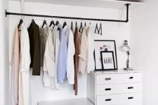 03 a small makeshift closet with dressers, a holder for hangers, an open shelf right in the bedroom