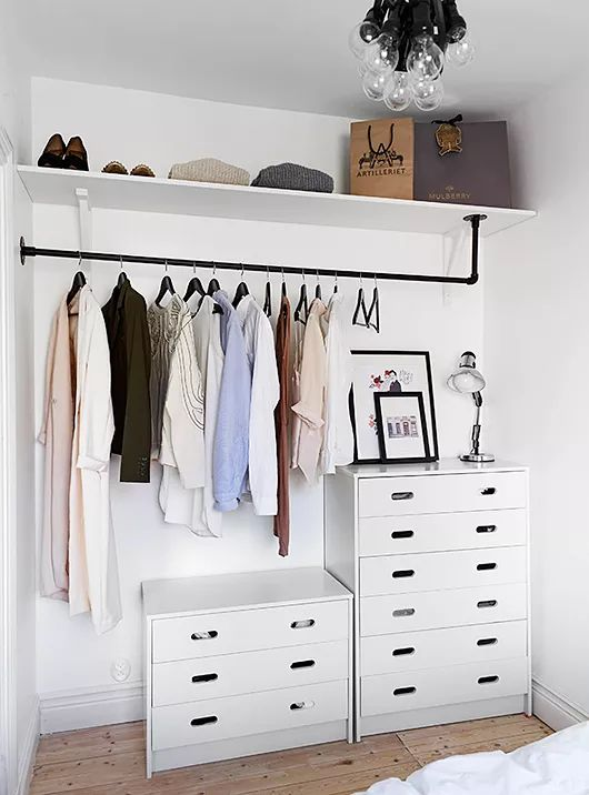 a small makeshift closet with dressers, a holder for hangers, an open shelf right in the bedroom