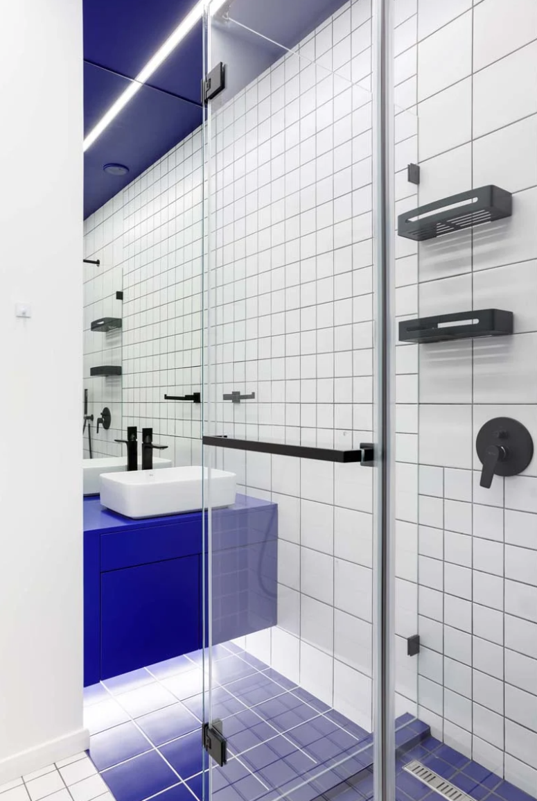 Black fixtures highlight the graphic effect and a bright blue vanity adds color
