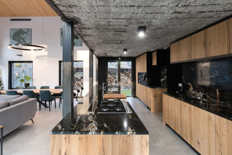 The kitchen is large, it's done in neutral stained wood and black stone plus a concrete ceiling