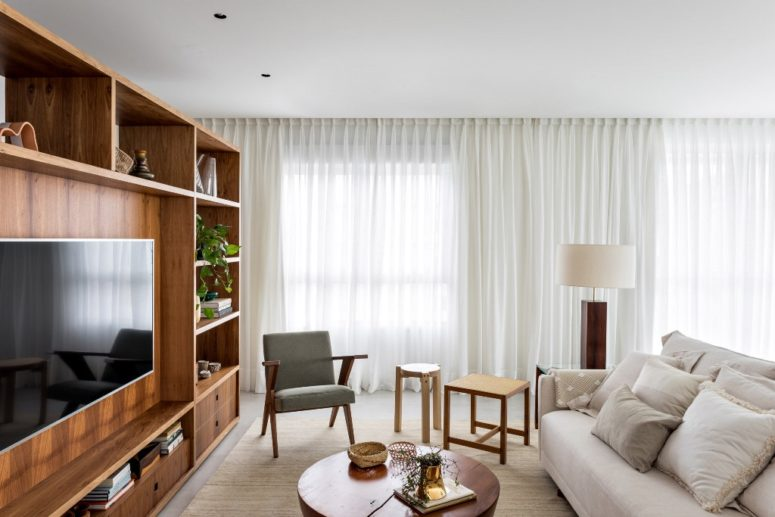 The living room is done with a large wooden unit for storage that divides the spaces, some comfy modern furniture and airy curtains