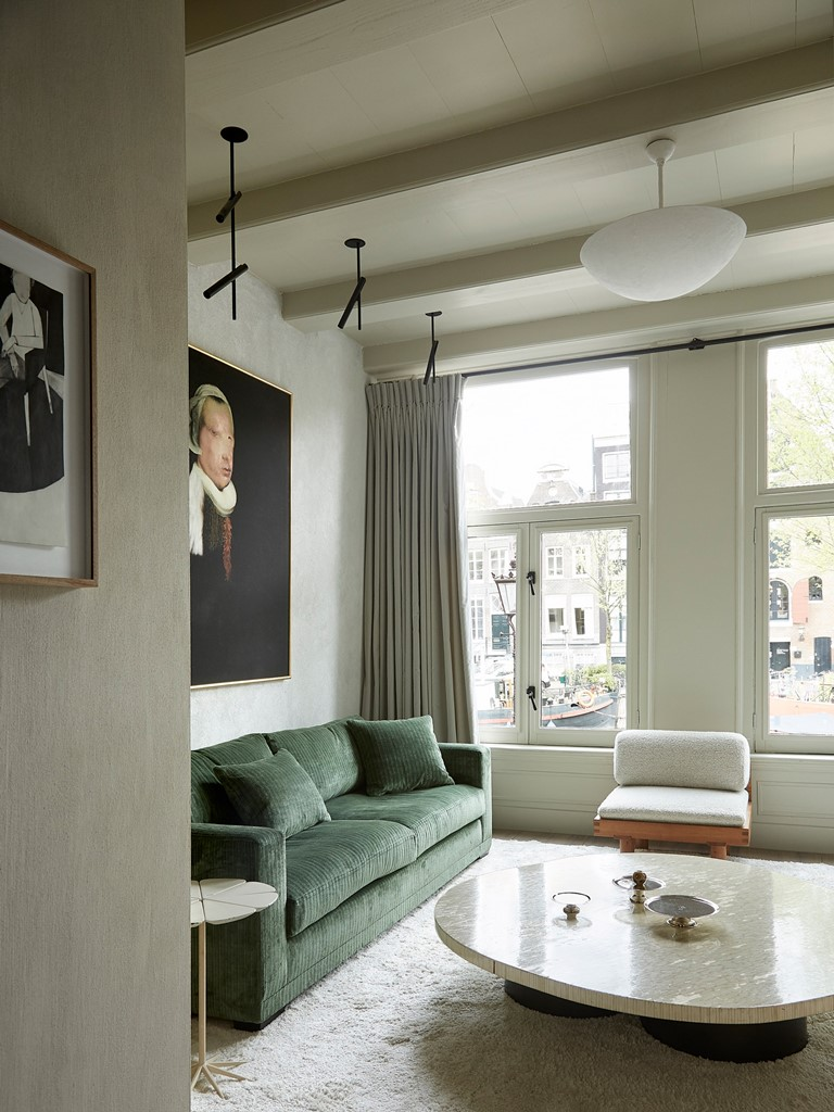 The living room is full of light, the furniture is neutral and muted-colored, there are artworks